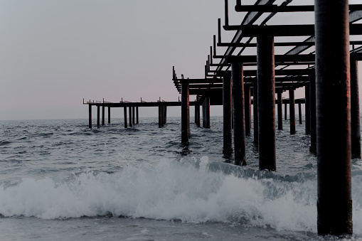 metal and wood jetty over wavy sea