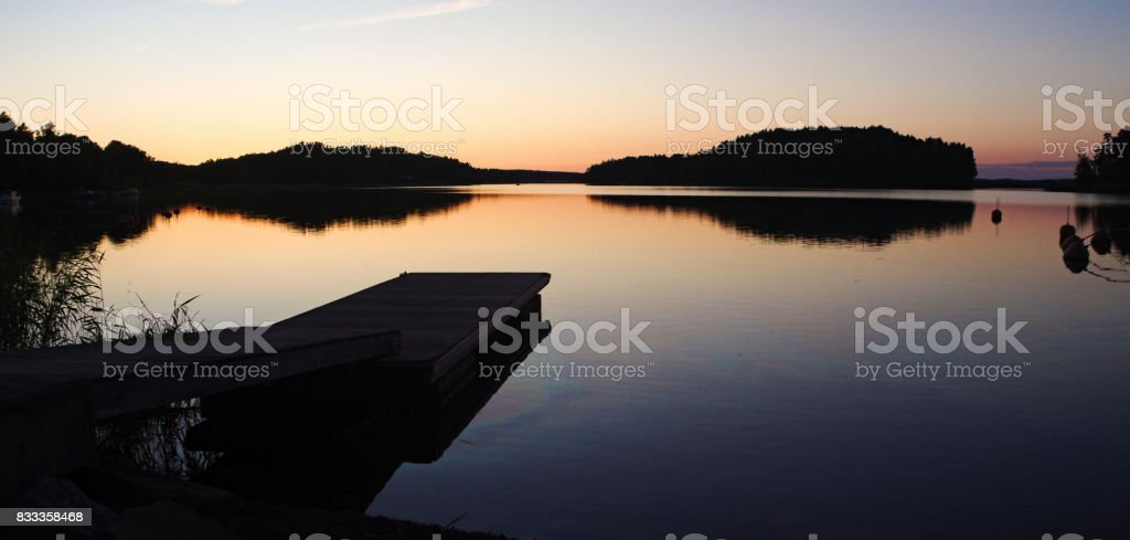 A jetty reflected in the still water at sunset, wet footprints on the jetty stock photo
