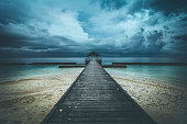 jetty under dramatic sky at maldives islands, indian ocean.