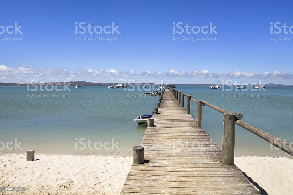Jetty with blue water and white sand stock photo