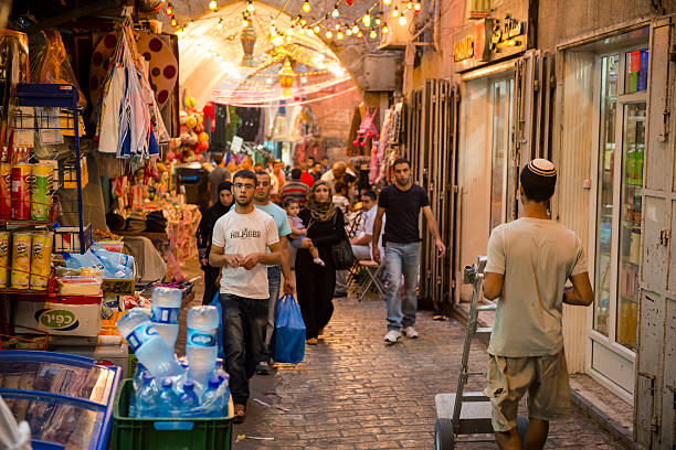 Jew and Arab in Jerusalem's Muslim Quarter East Jerusalem, Israel - July 24, 2013: A Jewish man wearing a yarmulke walks on the same street as Palestinian men and women in the Muslim Quarter of Jerusalem's Old City. Photo taken during Ramadan. muslim quarter stock pictures, royalty-free photos & images