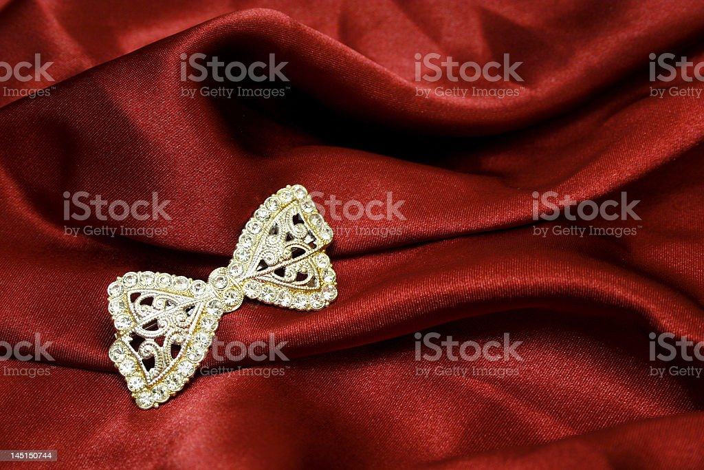 Jewel bow on red silk royalty-free stock photo