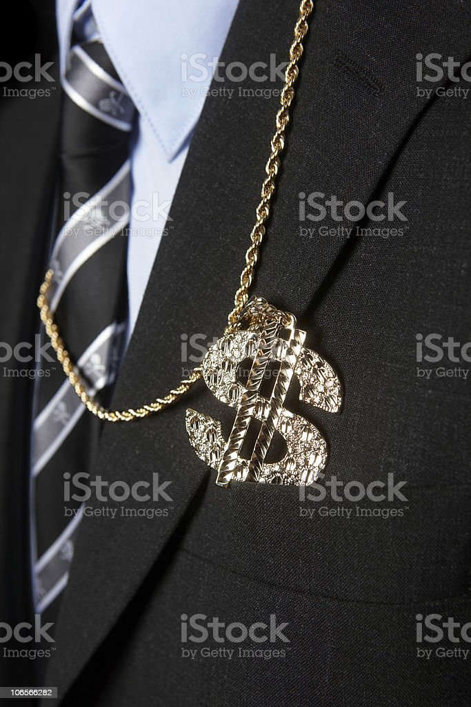 A jeweled dollar sign on a chain tucked into a suit pocket stock photo
