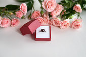 istock Jeweled engagement ring in opened red jewelry box surrounded with pale pink roses. Valentine's day celebrating 1292441156