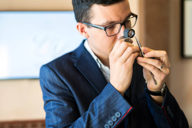 Jeweler examining diamond through loupe Jeweler examining diamond thoroughly through loupe jeweller stock pictures, royalty-free photos & images