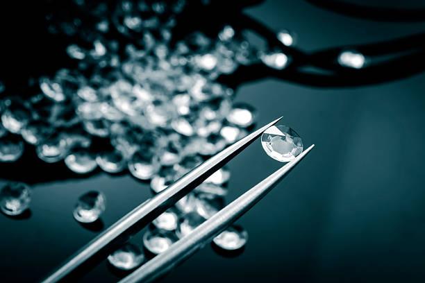 Jeweler inspecting a diamond with tweezers stock photo