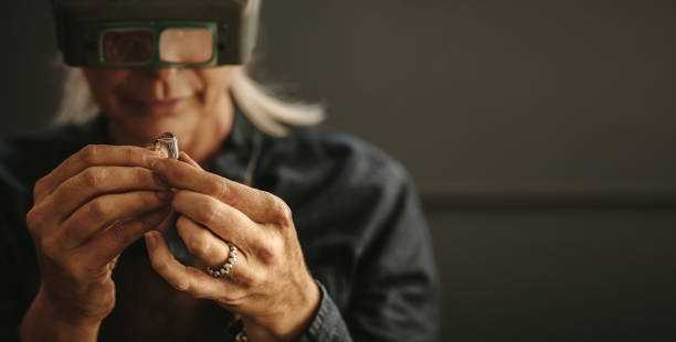 Jeweler inspecting diamond ring with magnifying glass Female goldsmith inspecting jewelry using magnifying glass in workshop.  Woman jeweler inspecting diamond ring with magnifying glass. jeweller stock pictures, royalty-free photos & images