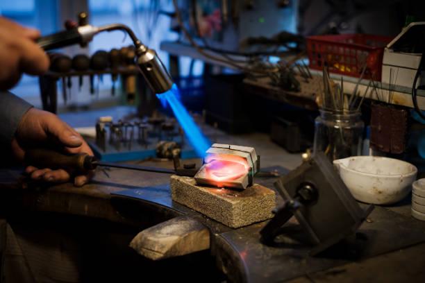 Juwelier schmilzt mit Flammsilber oder Gold auf alter Werkbank – Foto