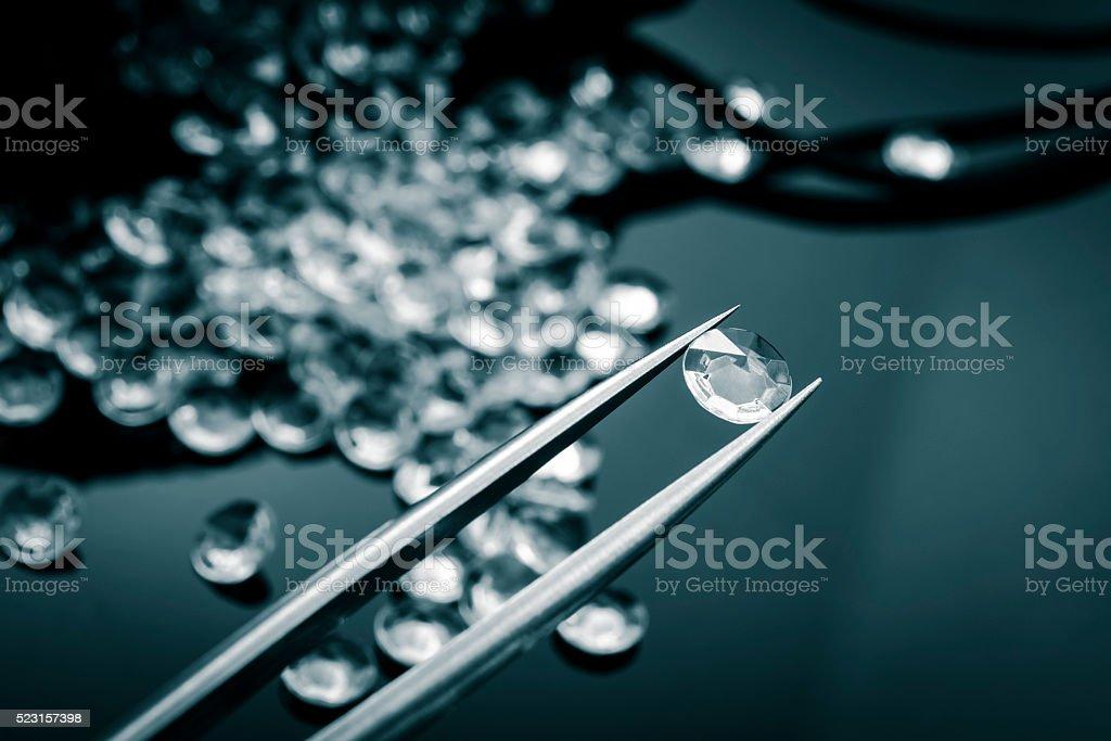Jeweler observing a diamond with tweezers stock photo