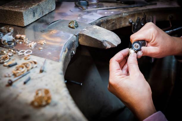 Juwelier poliert Goldring auf alter Werkbank in Schmuckwerkstatt – Foto