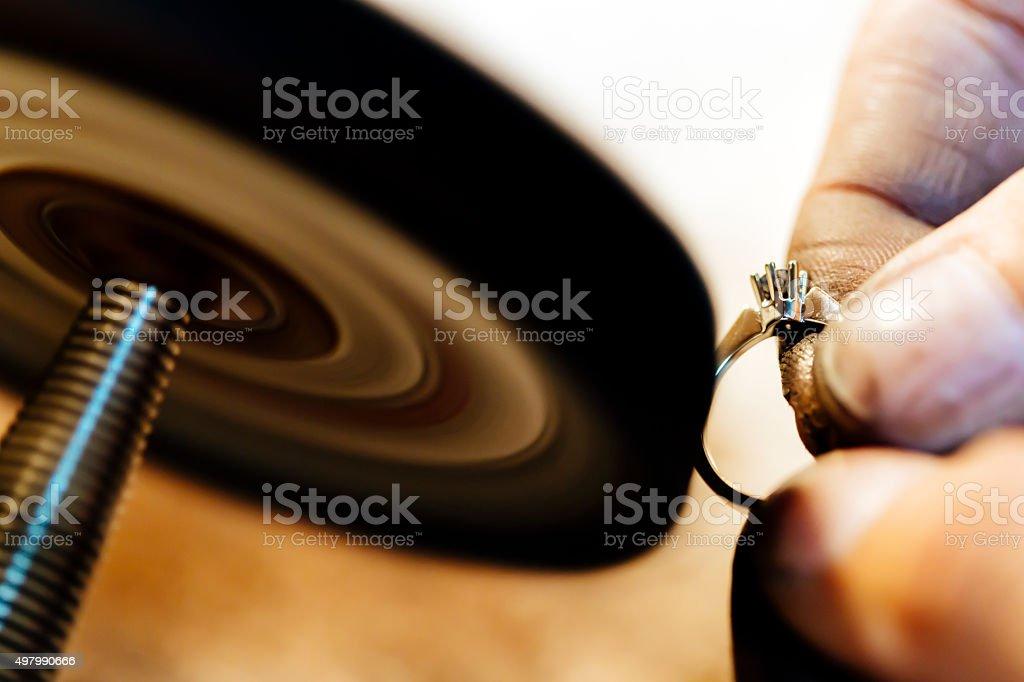 Jeweler polishing jewelry stock photo