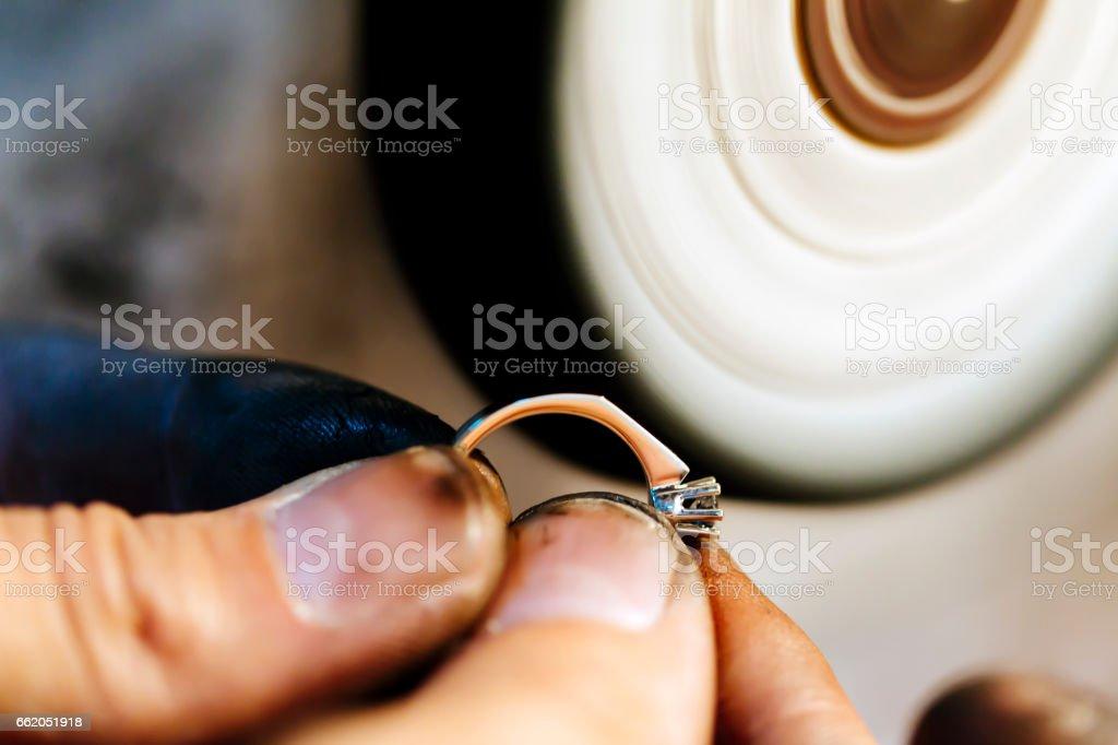 Jeweler polishing jewelry with tools royalty-free stock photo