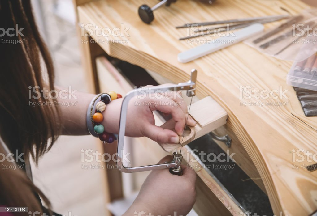 Jeweler Using Saw To Create Jewelry Stock Photo - Download
