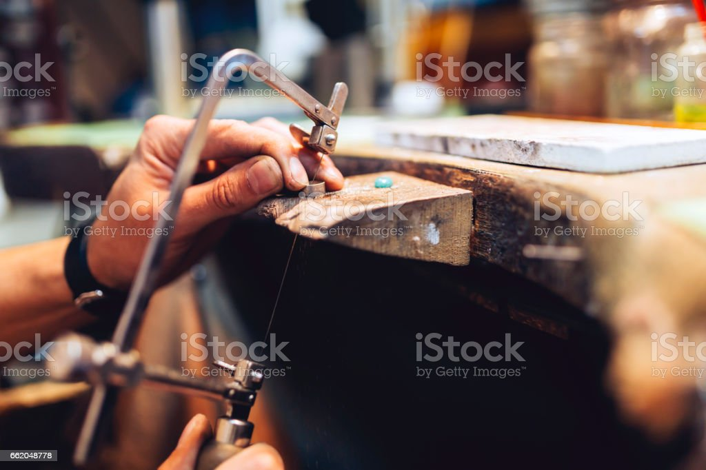 Jeweler using saw to create jewelry royalty-free stock photo