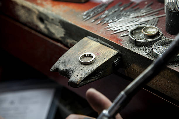 jeweler's bench with wedding band - diamond ring hand stock pictures, royalty-free photos & images
