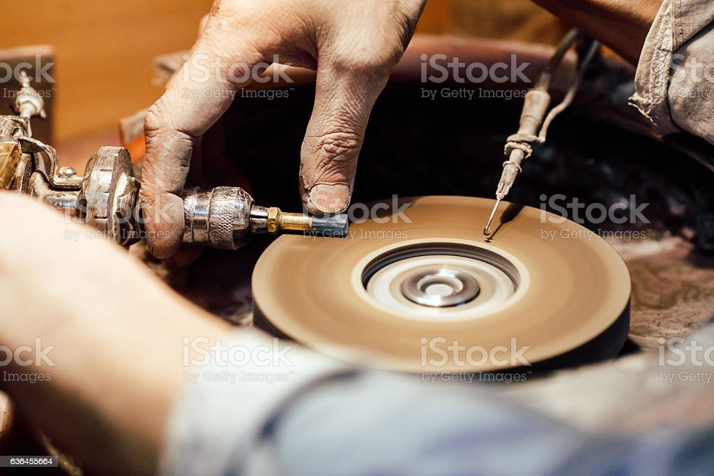 Jeweller polishing a stone blue cubic zirconia stock photo