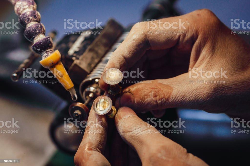 Jewellery polishing a stone blue cubic zirconia stock photo
