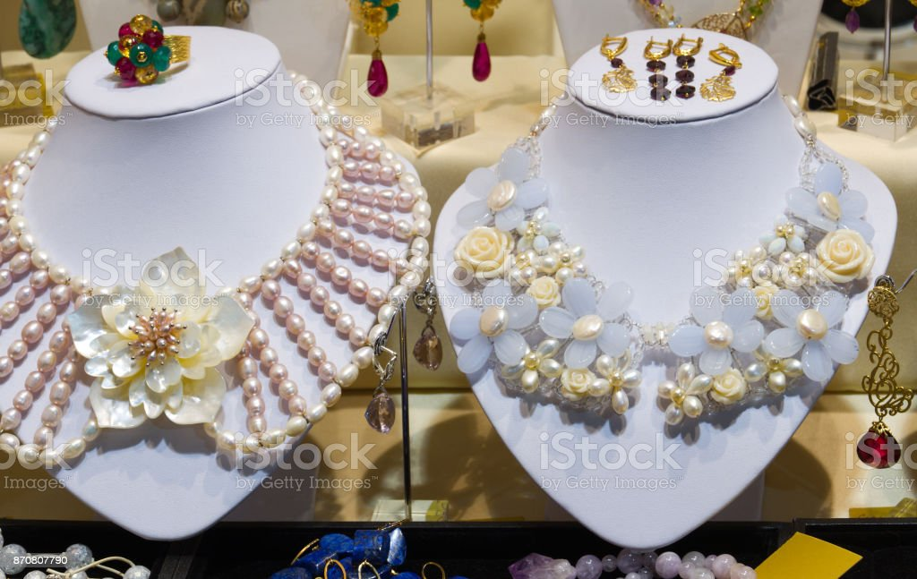 Jewellery storefront (shopwindow) with decorations: colorful beads and necklaces of gems, perls and different stones. stock photo