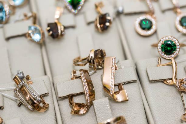 schmuck mit edelsteinen im showcase im store - diamanten kaufen stock-fotos und bilder