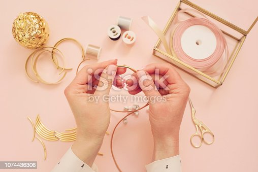 1074436306istockphoto Jewelry designer workplace. Woman hands making handmade jewelry. Freelance fashion femininity workspace in flat lay style. Pastel pink and gold 1074436306