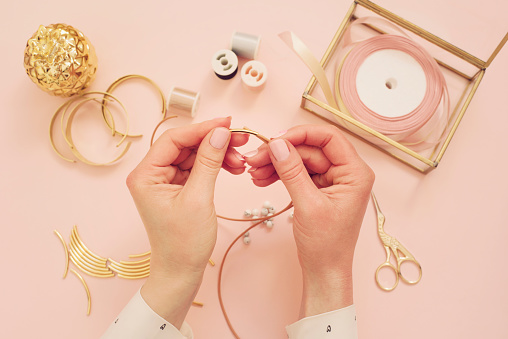 istock Jewelry designer workplace. Woman hands making handmade jewelry. Freelance fashion femininity workspace in flat lay style. Pastel pink and gold 1074436306