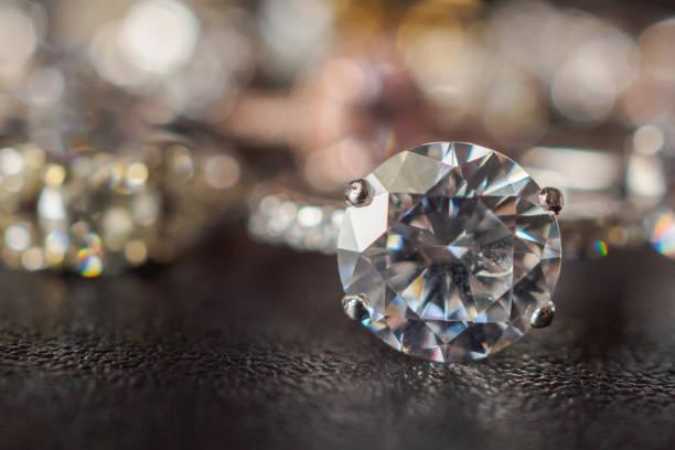 schmuck diamantringe auf schwarzem hintergrund hautnah - diamantschmuck stock-fotos und bilder