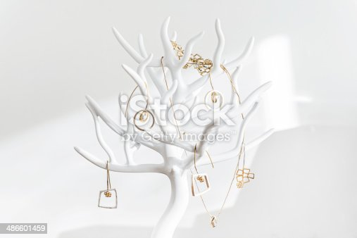 White jewelry display, stand hanger in the shape of tree with gold jewelery is standing on the shelf.