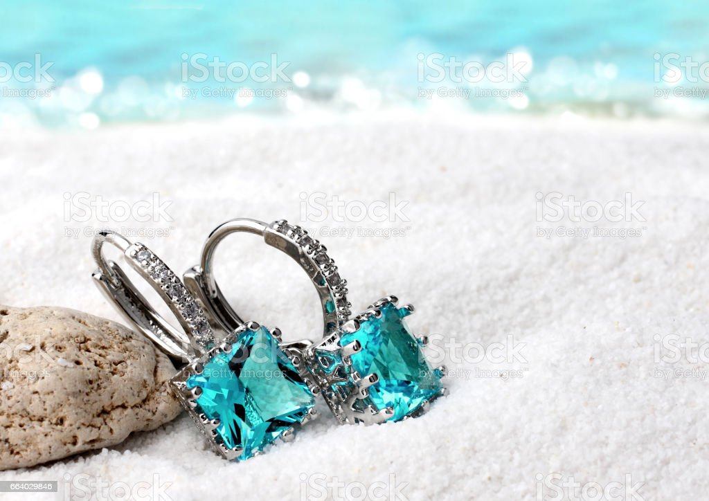 Jewelry earrings with aquamarine on sand beach background, soft focus stock photo