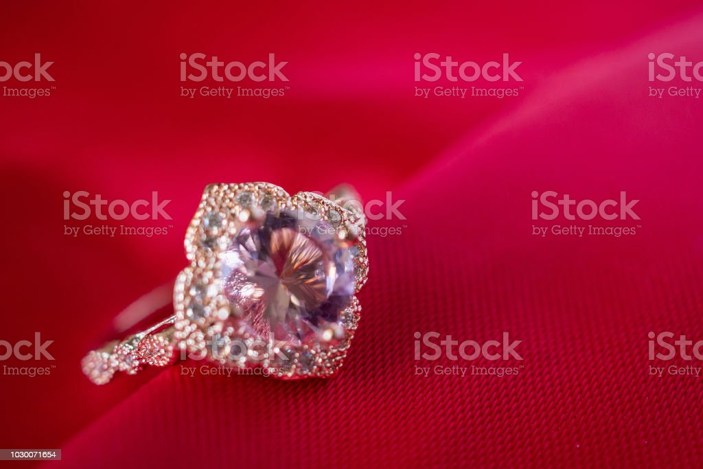 Jewelry luxury pink gold ring with sapphire gemstone on red fabric...