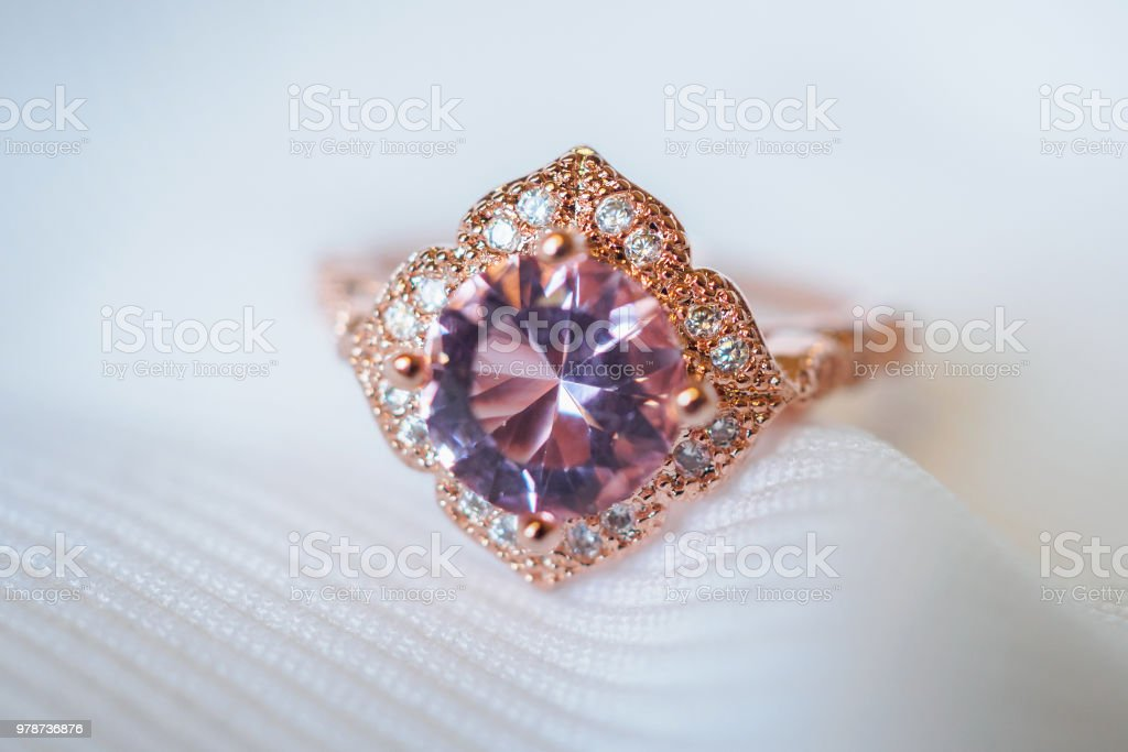 Jewelry luxury pink gold sapphire gemstone ring on white fabric...