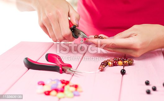 1074436306istockphoto Jewelry making. Female hands with a tool on a pink table. 1133605135