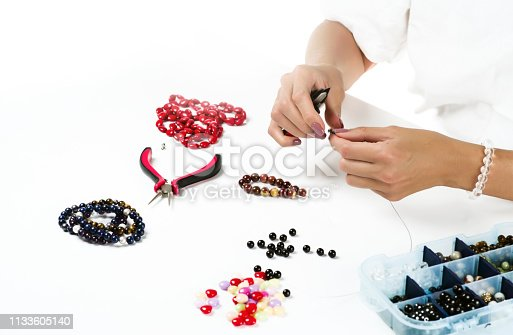 1074436306istockphoto Jewelry making. Female hands with a tool on a white background 1133605140
