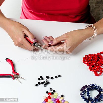 1074436306istockphoto Jewelry making. Female hands with a tool on a white background 1136216898