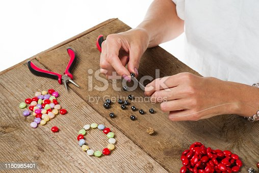 1074436306istockphoto Jewelry making. Making a bracelet of colorful beads. Female hands with a tool on a rough wooden table. 1150985401
