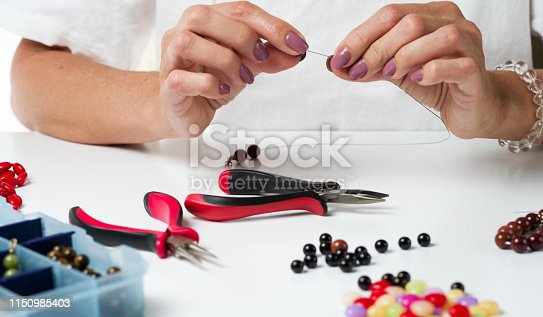 1074436306istockphoto Jewelry making. Making a bracelet of colorful beads. Female hands with a tool. 1150985403