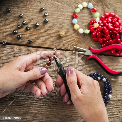 1074436306istockphoto Jewelry making. Making a bracelet of colorful beads. Female hands with a tool on a rough wooden table. 1168797856