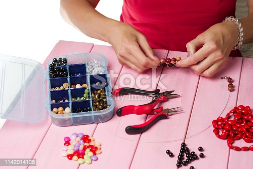 1074436306istockphoto Jewelry making. Making bracelet of colorful beads. Female hands with a tool on a pink background 1142014125