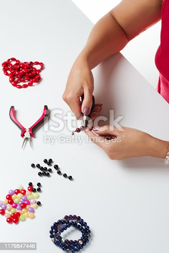 1074436306istockphoto Jewelry making. Making bracelet of colorful beads. Female hands with a tool on a white 1179847446