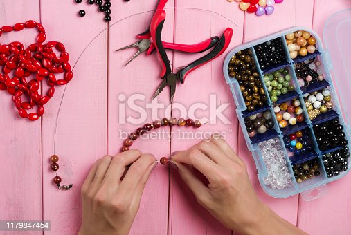 1074436306istockphoto Jewelry making. Making bracelet of colorful beads. Female hands with a tool on a pink 1179847454