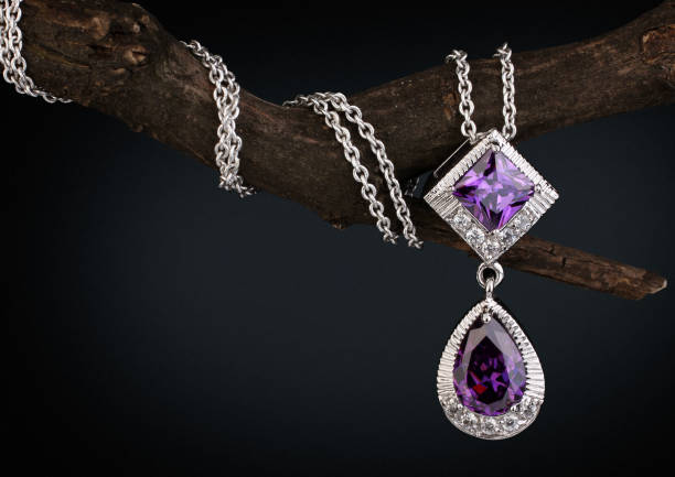 Jewelry  pendant witht gem  amethyst on twig, black background stock photo