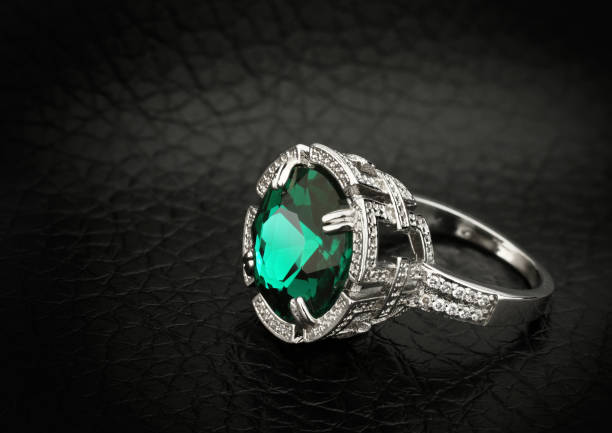 jewelry ring with big green gem on black leather background,  copy space stock photo