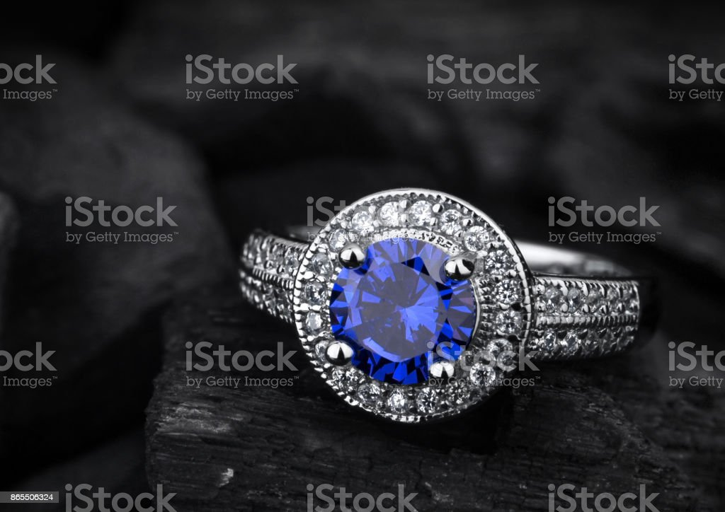 jewelry ring witht big blue sapphir on black coal background stock photo