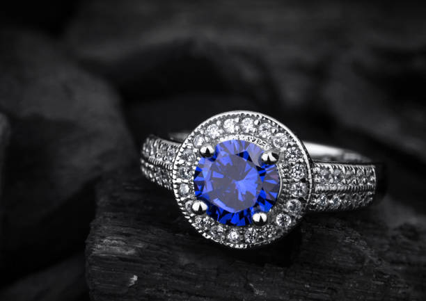 jewelry ring witht big blue sapphir on black coal background - ring jewelry stock photos and pictures