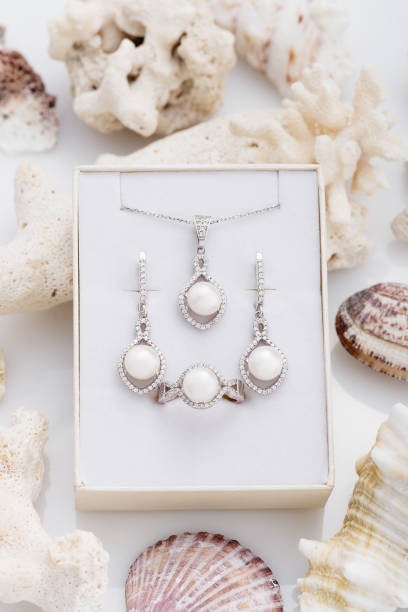 schmuck-set elegante silberne ohrringe, ring und anhänger halskette mit perlen und diamanten in geschenkbox auf coral - halskette weißgold stock-fotos und bilder