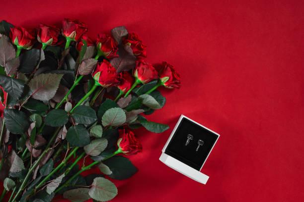 schmuck-set goldene ohrringe in einer geschenk-box und rote rosen auf rück - ohrringe rose stock-fotos und bilder
