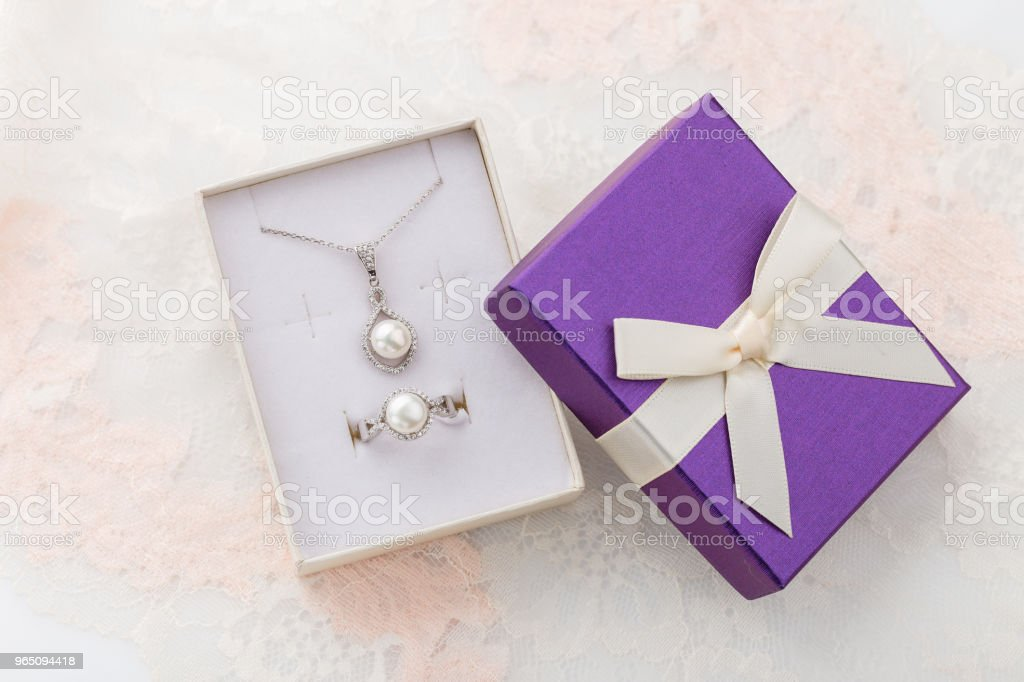 Jewelry set of pearl necklace and ring in purple gift box with bow on lace background zbiór zdjęć royalty-free
