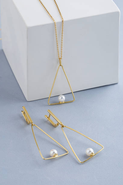 Jewelry set of triangle shape gold earrings and pendant necklace with pearls on gray background
