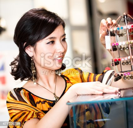 Asian woman at jewelry shop.