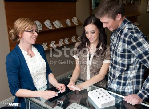 478253473istockphoto Jewelry store employee helping engaged couple 114366551