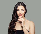 Jewelry woman. Young woman with makeup, long curly hair and diamond ring, necklace and earrings